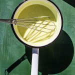 Calamansi Curd in a sauce pan with a whisk.