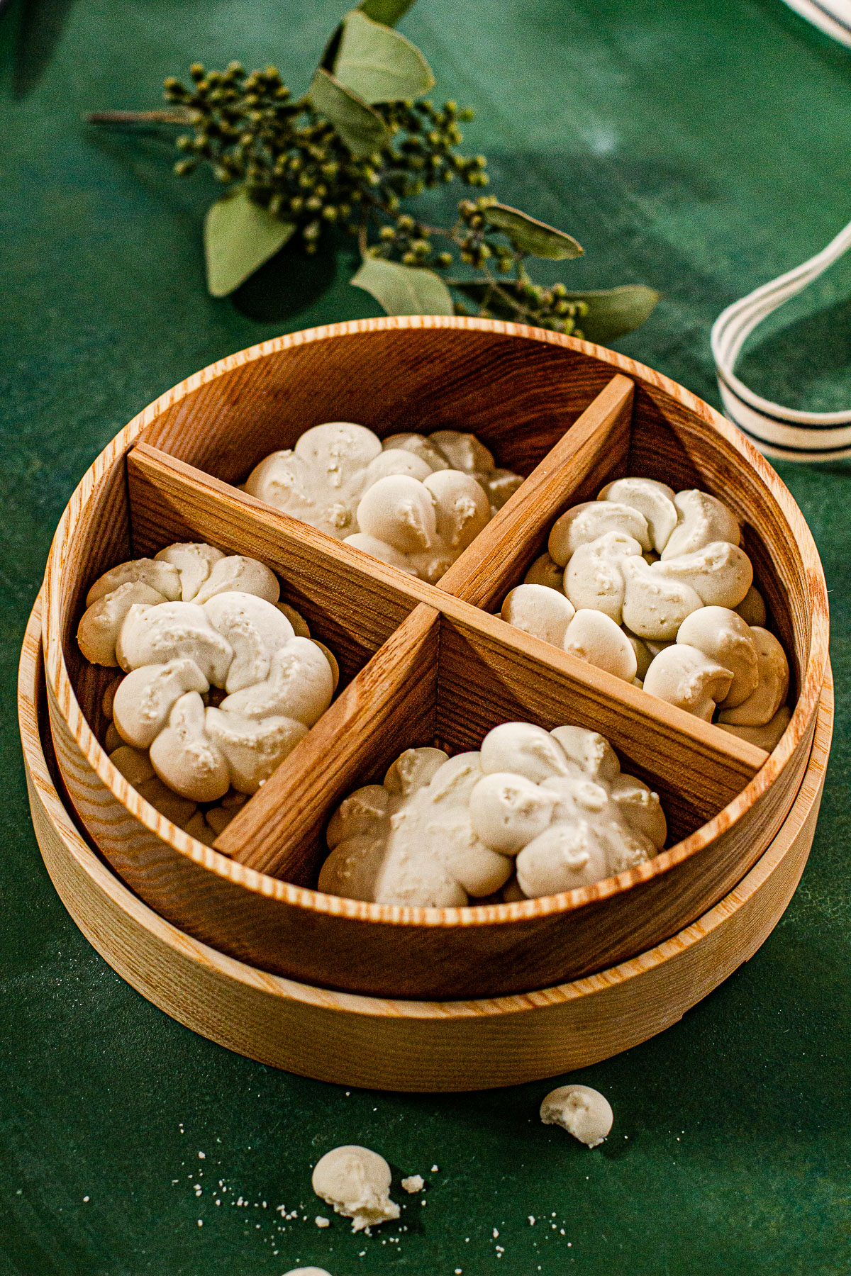 Uraro (Arrowroot) Cookies In a wooden cookie box on a green backdrop.